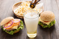 Beer being poured into glass with gourmet hamburgers and french Royalty Free Stock Photo