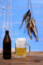 Beer on blue background dried rudd fish mug of with fishing net Royalty Free Stock Images