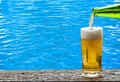 Beer with blue water ripple on background Royalty Free Stock Photography