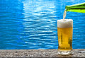 Beer with blue water ripple on background Royalty Free Stock Photos