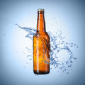 Beer bottle with water splash on blue Royalty Free Stock Photos
