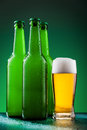 Beer bottles with full glass against vivid background Royalty Free Stock Images