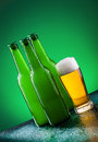 Beer bottles with full glass against vivid background Stock Image