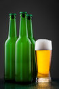 Beer bottles with full glass against vivid background Royalty Free Stock Photos