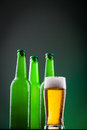 Beer bottles with full glass against vivid background Stock Photo