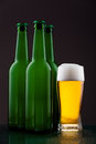 Beer bottles with full glass against vivid background Royalty Free Stock Photo