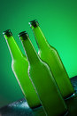 Beer bottles three against vivid green background Royalty Free Stock Photography