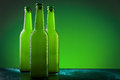 Beer bottles three against vivid green background Stock Photo