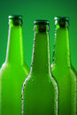 Beer bottles three against vivid green background Stock Photography