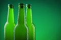 Beer bottles three against vivid green background Stock Photos