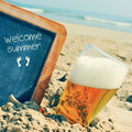 Beer and chalkboard with the text welcome summer, on the sand of Royalty Free Stock Photo