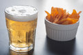 Beer and chips close up of glass lager a cup of corn Royalty Free Stock Photo