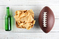 Beer chips and football bottle bowl of an american style on a rustic whitewashed wood surface horizontal format the bottle is Royalty Free Stock Photos