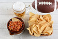 Beer chips and salsa high angle shot of a bowl of corn a crock full of fresh a mug of an american football on a whitewashed rustic Royalty Free Stock Photo