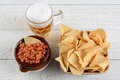 Beer chips and salsa high angle shot of a bowl of corn a crock full of fresh mug of on a whitewashed rustic wood table horizontal Royalty Free Stock Image