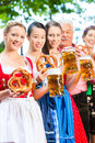 Beer garden friends drinking in bavaria pub men and women tracht dirndl and lederhosen a fresh germany Royalty Free Stock Image