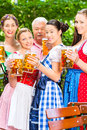 Beer garden friends drinking in bavaria pub men and women tracht dirndl and lederhosen a fresh germany Stock Photo