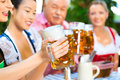 In beer garden friends drinking beer in bavaria tracht dirndl and lederhosen a fresh germany Stock Photo