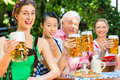 In beer garden friends drinking beer in bavaria tracht dirndl and lederhosen a fresh germany Royalty Free Stock Photography