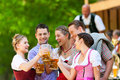 In beer garden friends in front of band bavaria germany tracht dirndl and lederhosen and dirndl standing Stock Photos