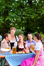 In beer garden friends on a table with beer tracht dirndl and and snacks bavaria germany Royalty Free Stock Photography