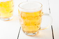 Beer in glass beer mug light on white wooden table Royalty Free Stock Images