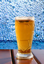 Beer glass on wooden table on blue water drips background taken closeup Royalty Free Stock Photos