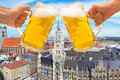 Beer mugs cheers with Munich Marienplatz in background Royalty Free Stock Photo