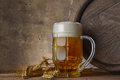 Beer mug with wheat ears and wooden barrel on a dark wall background, pour beer Royalty Free Stock Photo
