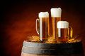 Beer mugs three with golden on a wooden barrel Stock Images