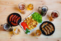 Beer, plate of roasted potato and frying pans with grilled sausages Royalty Free Stock Photo