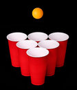 Beer pong red plastic cups and orange table tennise ball over black background closeup Royalty Free Stock Images
