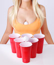 Beer pong. Red plastic cups with ping pong ball and blonde girl in tank top Royalty Free Stock Photo