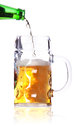 Beer pouring from bottle into mug Royalty Free Stock Photo