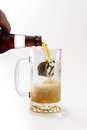 Beer pouring into mug golden foaming being poured on white background Royalty Free Stock Photo
