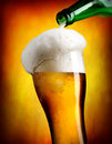 Beer pouring in tumbler from bottle on orange background Stock Images