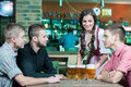 Beer pub for gentlemen beautiful young waitress serving while three men sitting at the table in Royalty Free Stock Photos