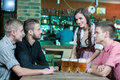 Beer pub for gentlemen beautiful young waitress serving while three men sitting at the table in Stock Photo