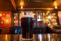 Beer at pub glass of dark in setting Royalty Free Stock Images