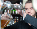 Beer pub man hand pouring of behind the bar Stock Images