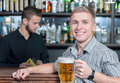 Beer pub man in handsome young men holding a mug and smiling while bartender pouring on the background Stock Image