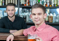 Beer pub man in handsome young men holding a mug and smiling while bartender pouring on the background Stock Photography