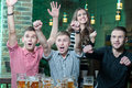 Beer pub three men and one girl with rejoice the victory of their favorite team in the Stock Images