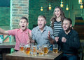 Beer pub three men and one girl with rejoice the victory of their favorite team in the Royalty Free Stock Image