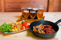 Beer, roasted potato and grilled sausages. Selective focus Royalty Free Stock Photo