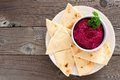 Beet hummus with pita bread on a plate over wood Royalty Free Stock Photo