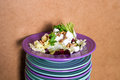 Beet salad with goat cheese, walnuts, greens and herbs and olive oil on a bright colorful ceramic plates stacked. Portion of salad
