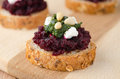 Beet salad with pesto and goat cheese on toasted grain breads on Stock Photos