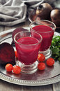 Beetroot smoothie in glass with fresh vegetables on round tray Stock Photo