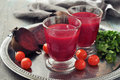Beetroot smoothie in glass with fresh vegetables on round tray Stock Image